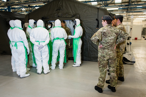 Pictured: A doctor briefs his team before ward rounds in the Strensall training facility, watched by directing staff. Minister for the Armed Forced Mark Francois has praised military personnel going through medical training to help tackle Ebola in West Africa. Mr Francois witnessed mission training at the Army Medical Services Training Centre (AMSTC), at Strensall near York, which is designed to develop and assess the clinical and organisational procedures required, as more than 100 members of the British Army's 22 Field Hospital prepare to provide a 12-bed treatment unit for healthcare workers in Sierra Leone. Personnel carried out parts of the exercise in personal protective equipment in a hangar converted into a mock-up field hospital, treating simulated casualties to replicate the situation they expect to find when they deploy.